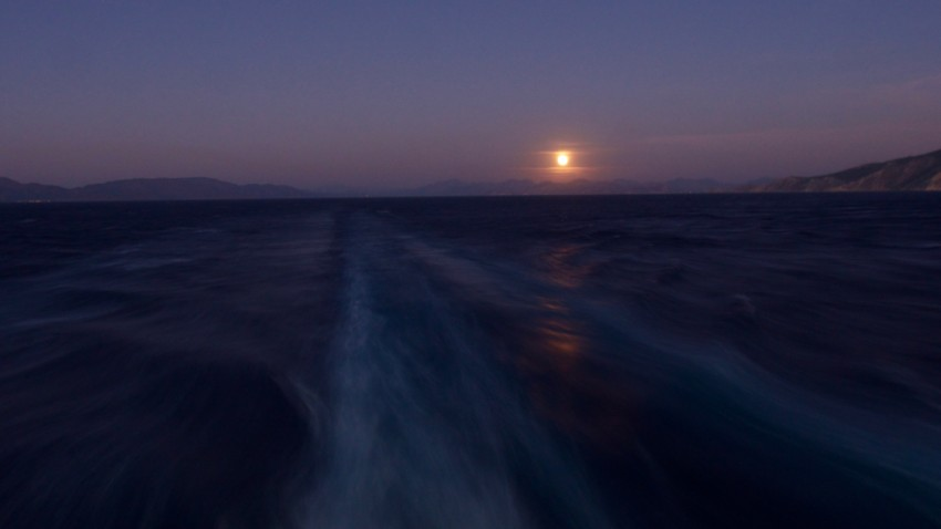 Seabourn Sojourn sails away from Symi with a full moon in our wake.