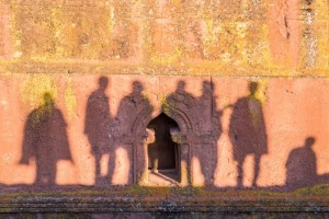 The shadows of the people on the side of an ancient church.