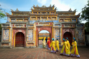 People in traditional costumes walk under an archway in the Imperial City of Hue, Vietnam