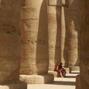 Man and woman sitting on limestone pillar at the Karnak Temple Complex