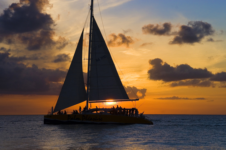 Beautiful sailboat back lit by a stunning sunset, Eagle Beach, Aruba.