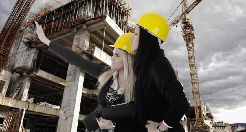 Two women contruction workers looking building under construction