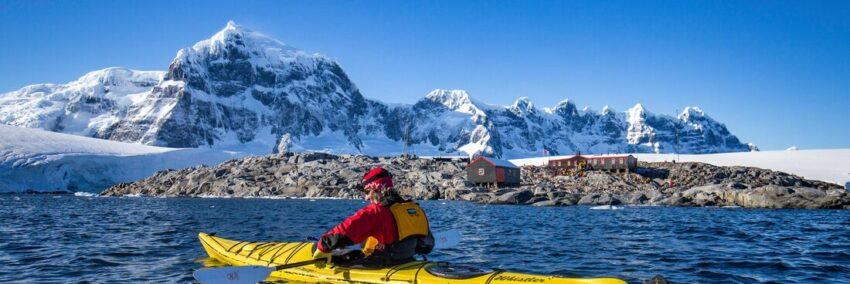 Person rowing kayak with icy mountains in background