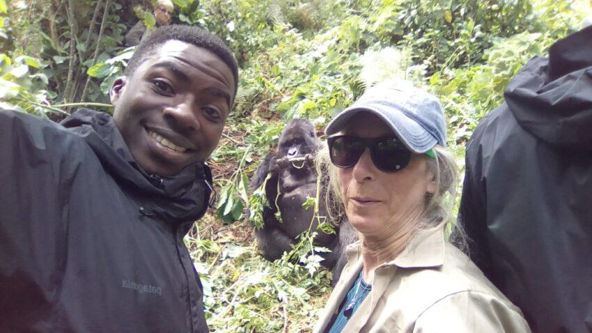 two people selfie with gorilla in wild