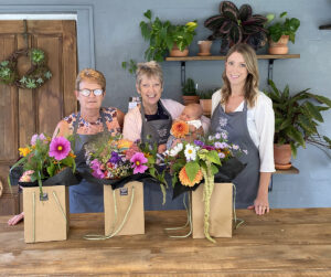 Three women in front of bags of bright flowers
