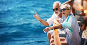 Older couple leaning over railing on cruise ship